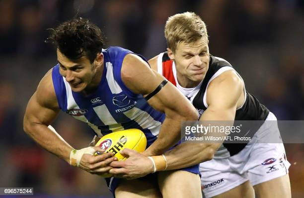 Robbie Tarrant of the Kangaroos is tackled by Nick Riewoldt of the Saints during the 2017 AFL round 13 match between the North Melbourne Kangaroos...