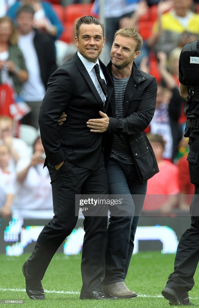 Robbie Williams (L) and former 'Take That' band mate Garry Barlow walk on the pitch before the Unicef Soccer Aid charity football match at Old Trafford in Manchester, north-west England on June 6, 2010. Soccer Aid is the brainchild of Robbie Williams and all money raised through profits from ticket sales and donations made by viewers of the english channel ITV during the match will go to UNICEF�s invaluable work helping children around the world.