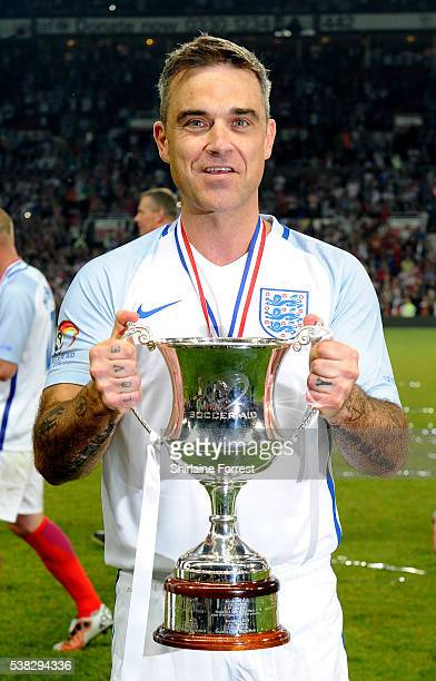 Robbie Williams celebrates winning as team captain of England during Soccer Aid at Old Trafford on June 5 2016 in Manchester England