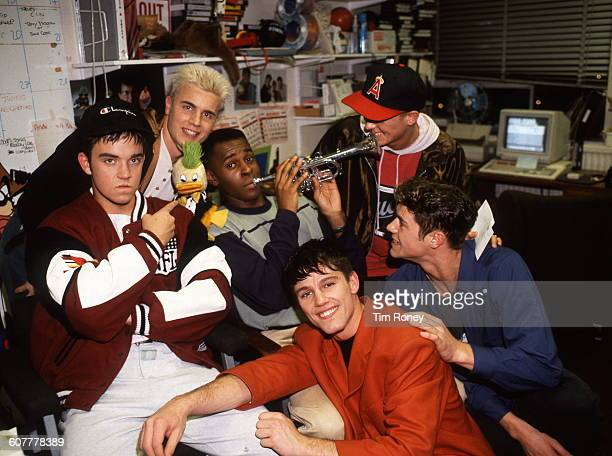 Robbie Williams Jason Orange Howard Donald Mark Owen and Gary Barlow of English pop group Take That pose with television presenter Andi Peters and...