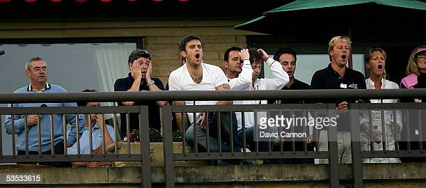 Robbie Williams of England watches the golf with Anthony McPartlin and Declan Donnelly and others during the monday fourball matches on the final day...