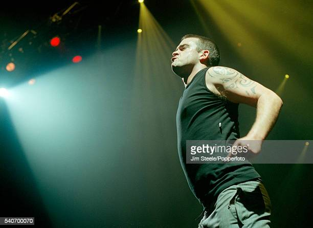 Robbie Williams performing on stage during the NetAid Concert held at Wembley Stadium in London on the 9th October 1999
