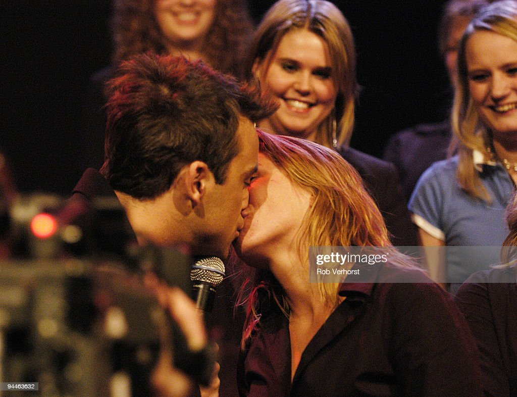 Robbie Williams performs live while kissing fans on the Dutch TV programme 'Pulse' at Hilversum Studios, Holland on December 09 2004