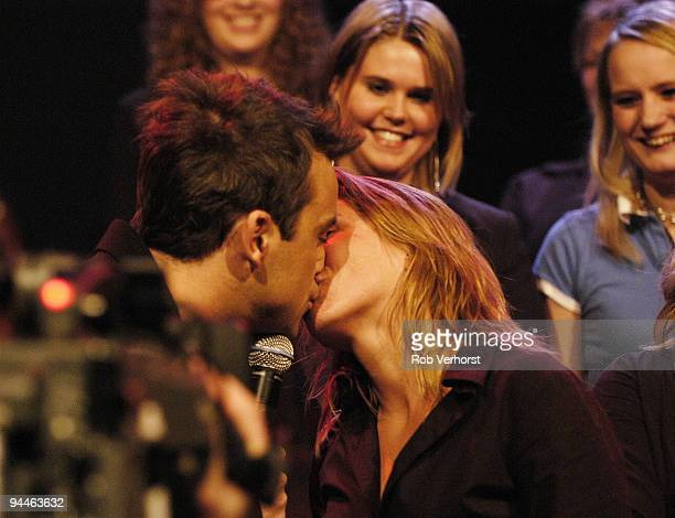 Robbie Williams performs live while kissing fans on the Dutch TV programme 'Pulse' at Hilversum Studios Holland on December 09 2004