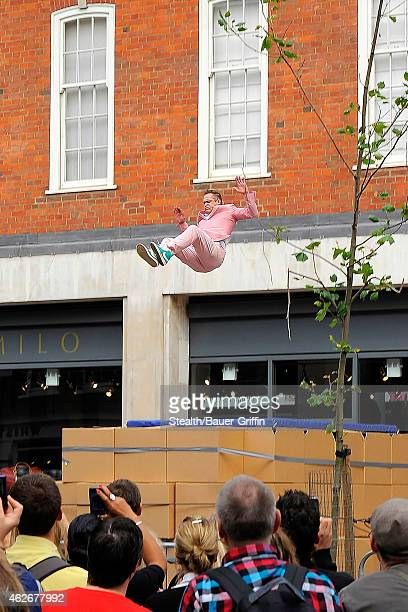 Robbie Williams' stuntman is seen jumping from a roof during filming of a stunt scene his music video 'Candy' on August 17 2012 in London United...