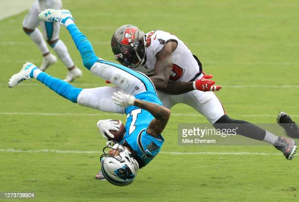 Robby Anderson of the Carolina Panthers is upended as he is tackled by Jason Pierre-Paul and Sean Murphy-Bunting of the Tampa Bay Buccaneers during...