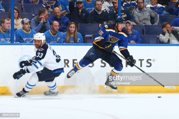 Robby Fabbri of the St Louis Blues controls the puck against Dustin Byfuglien of the Winnipeg Jets at the Scottrade Center on January 31 2017 in St...