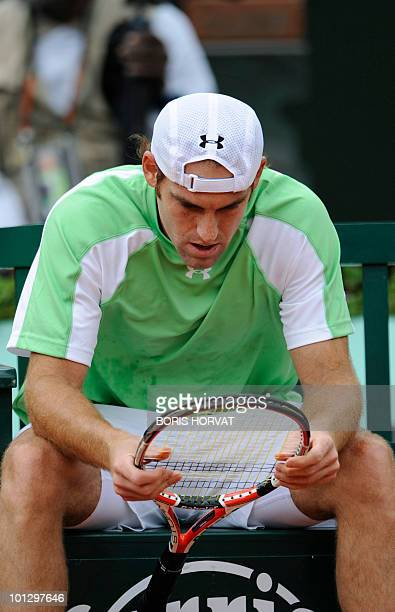 US Robby Ginepri inspects his raquet during his men's fourth round match against Serbia's Novak Djokovic in the French Open tennis championship at...
