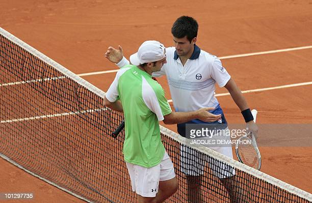 US Robby Ginepri is greeted at the net by Serbia's Novak Djokovic after losing their men's fourth round match in the French Open tennis championship...