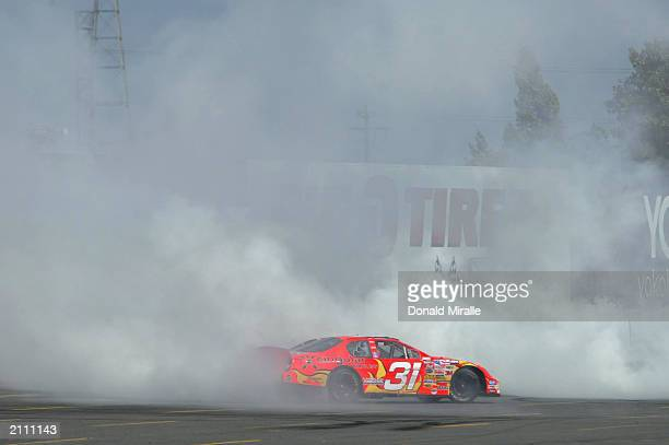 Robby Gordon driver of the CIngular Wireless Chevrolet Monte Carlo spins doughnuts in his car after winning the NASCAR Winston Cup Dodge Save Mart...
