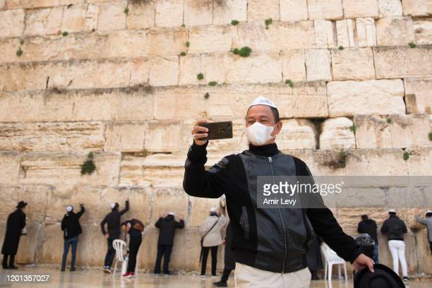 Robby Robyanto, tourist from Indonesia, takes a photo as he wears a face mask during a mass prayer at the Western Wall for coronavirus patients in...