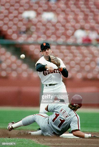 Robby Thompson of the San Francisco Giants gets his throw off to complete the double play over the top of John Kruk of the Philadelphia Phillies...