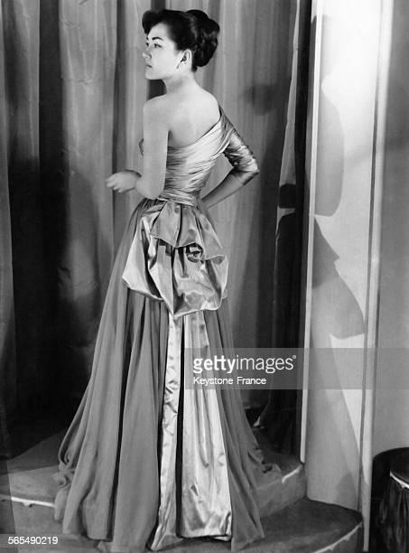 Robe du soir 'Aurore' faite de mousseline grise avec corsage de satin gris et rose les plis de la jupe ample sont reportés vers le dos et dissimulés...