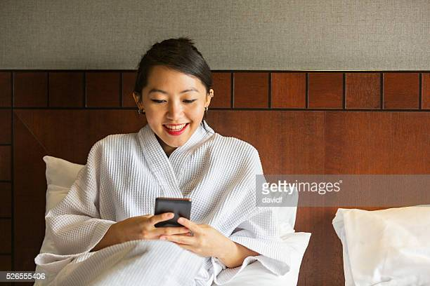 Robe Wearing Young Asian Woman Using a Mobile Phone Indoors