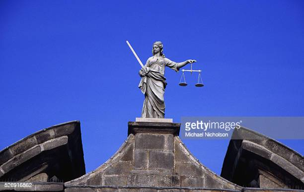 A robed figure armed with sword and scales the symbols of justice stands above a gateway at Dublin Castle in the old part of Dublin Republic of...