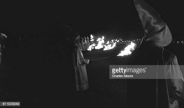 Robed Ku Klux Klan members hold torches as they stand in a large circle during one of the organization's outdoor nighttime rallies Salisbury North...