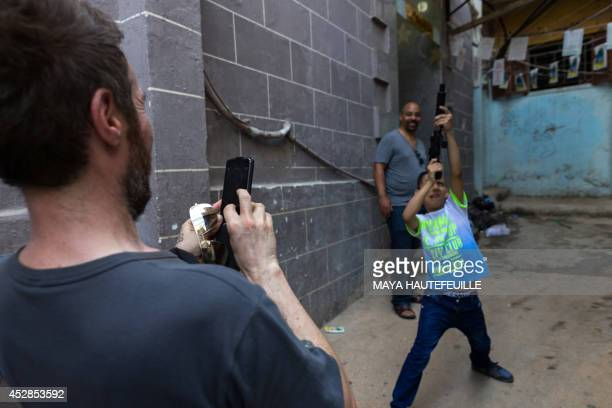 Robert '3D' del Naja of British triphop band Massive Attack takes a picture of a Palestinian child with toy gun during an unofficial visit to the...