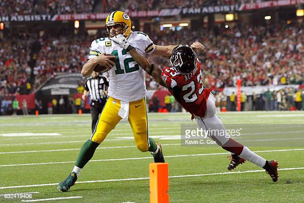 Robert Alford of the Atlanta Falcons attempts to tackle Aaron Rodgers of the Green Bay Packers in the fourth quarter in the NFC Championship Game at...