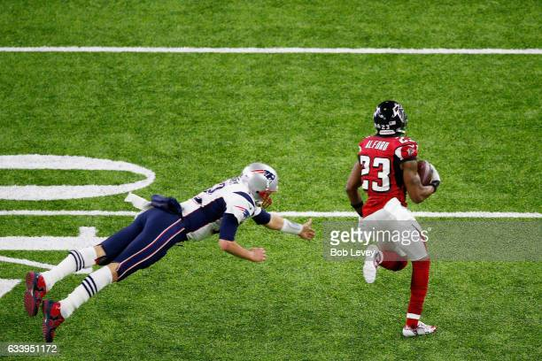 Robert Alford of the Atlanta Falcons runs past Tom Brady of the New England Patriots to score a touchdown on an 82 yard interception return against...