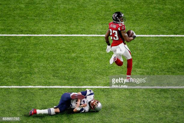 Robert Alford of the Atlanta Falcons runs past Tom Brady of the New England Patriots on his way to scoring a touchdown on an 82yard interception...