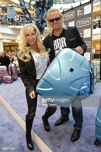 Robert And Carmen Geiss pose with a Titan suitcase during the opening event of a new Titan Shop on June 2 2014 in Osnabruck Germany