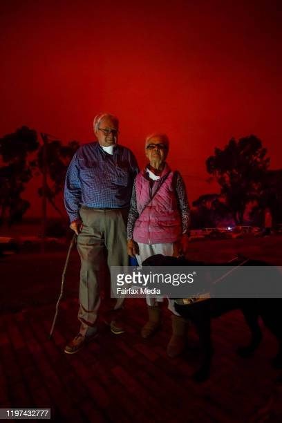 Robert and Karen Allen with dog Panther as day turns to a blood red sky in Mallacoota with the South Westerly change sparking up fire activity in the...