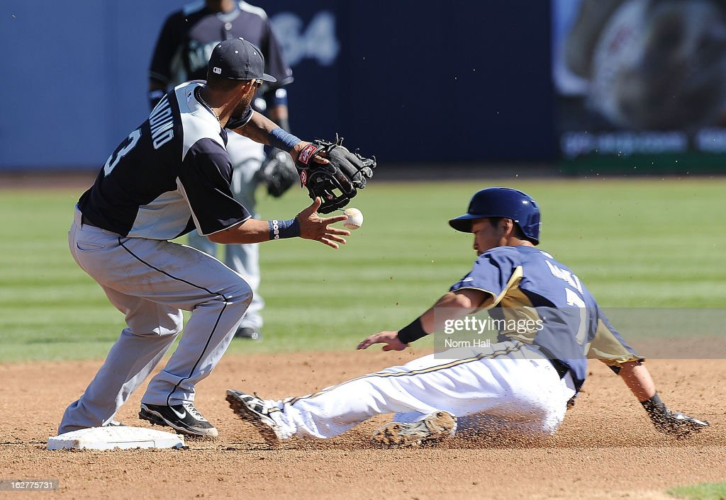 Robert Andino #3 of the Seattle Mariners knocks down a bouncing ball as Norichka Aoki #7 of the Milwaukee Brewers slides into second base at Maryvale Baseball Park on February 26, 2013 in Maryvale, Arizona.