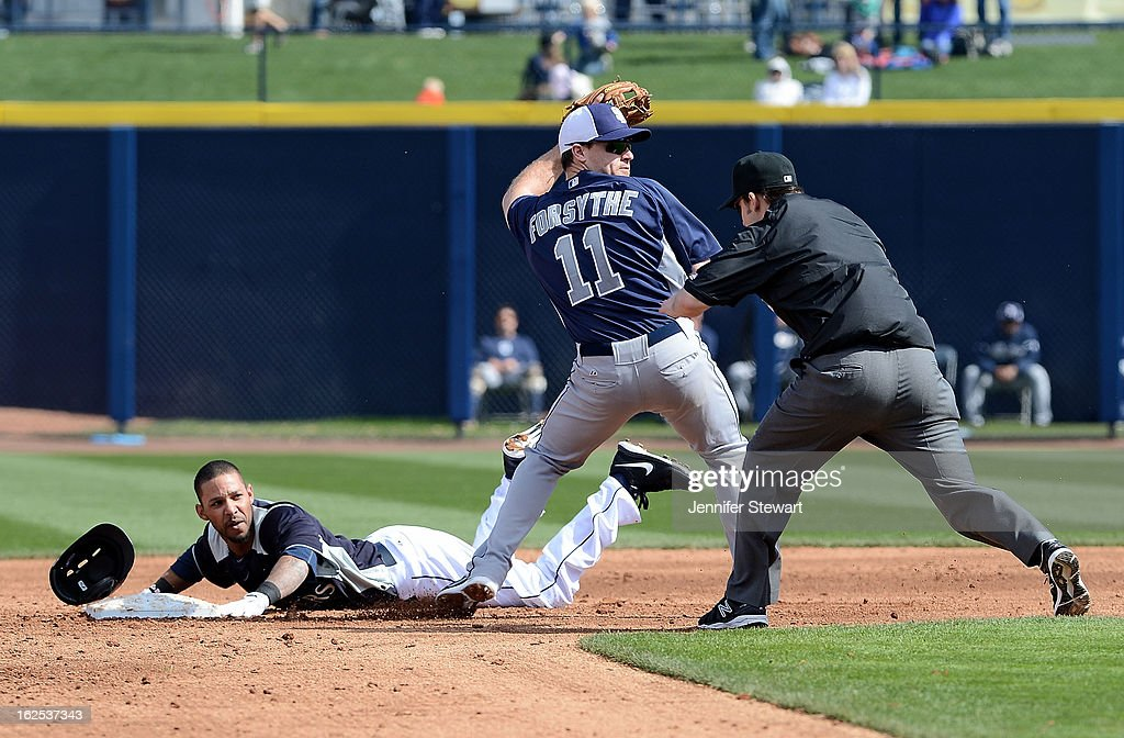 Robert Andino #3 of the Seattle Mariners safely slides into second base past the tag from infielder Logan Forsythe #11 of the San Diego Padres spring training game at Peoria Sports Complex on February 24, 2013 in Peoria, Arizona.