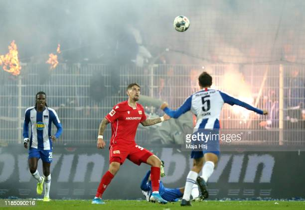 Robert Andrich of 1 FC Union Berlin battles for possession with Niklas Stark of Hertha BSC as fans set alight to clothing during the Bundesliga match...