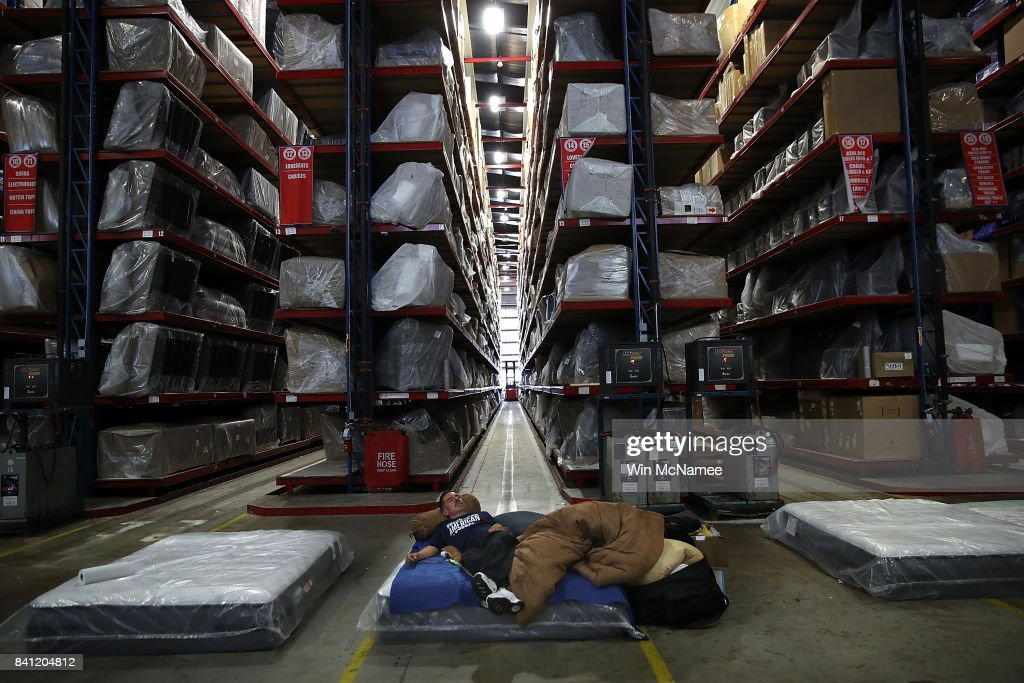 Robert Anthony Torres rests in the warehouse of Gallery Furniture, a local furniture store offering shelter to Hurricane Harvey evacuees August 31, 2017 in Houston, Texas. The city of Houston is still experiencing severe flooding in some areas due to the accumulation of historic levels of rainfall, though floodwaters are beginning to recede in many parts of the city.