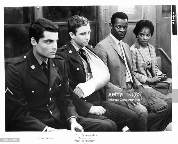 Robert Bannard sits on a bench with Beau Bridges who has his arm in a sling Brock Peters and Ruby Dee stares toward them in a scene from the film...