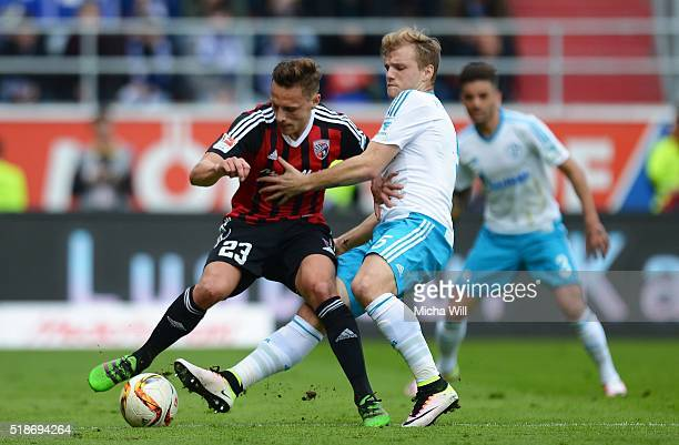 Robert Bauer of Ingolstadt and Johannes Geis of Schalke compete for the ball during the Bundesliga match between FC Ingolstadt and FC Schalke 04 at...