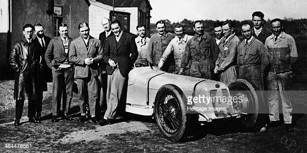 Robert Benoist with a cigarette leaning against a Delage 15S8 1927 A group of mechanics stand to the right of the car The racing drivers Albert Divo...