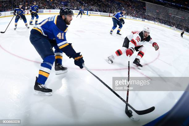 Robert Bortuzzo of the St Louis Blues and Marcus Johansson of the New Jersey Devils battle for the puck at Scottrade Center on January 2 2018 in St...