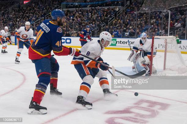 Robert Bortuzzo of the St Louis Blues and Noah Dobson of the New York Islanders battle for the puck at Enterprise Center on February 27 2020 in St...