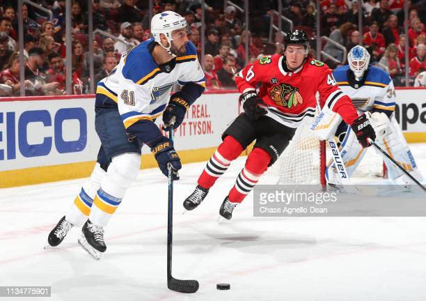 Robert Bortuzzo of the St Louis Blues approaches the puck ahead of John Hayden of the Chicago Blackhawks in the second period at the United Center on...