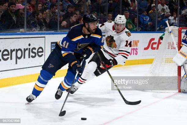 Robert Bortuzzo of the St Louis Blues handles the puck as Victor Ejdsell of the Chicago Blackhawks pressures at Scottrade Center on April 4 2018 in...
