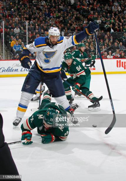 Robert Bortuzzo of the St Louis Blues is called for hooking on this play with Zach Parise of the Minnesota Wild during a game at Xcel Energy Center...