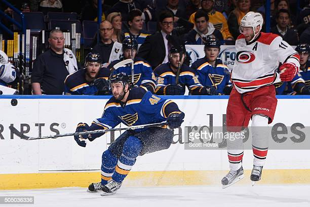 Robert Bortuzzo of the St Louis Blues looks to beat Jordan Staal of the Carolina Hurricanes to the puck at the Scottrade Center on January 14 2016 in...