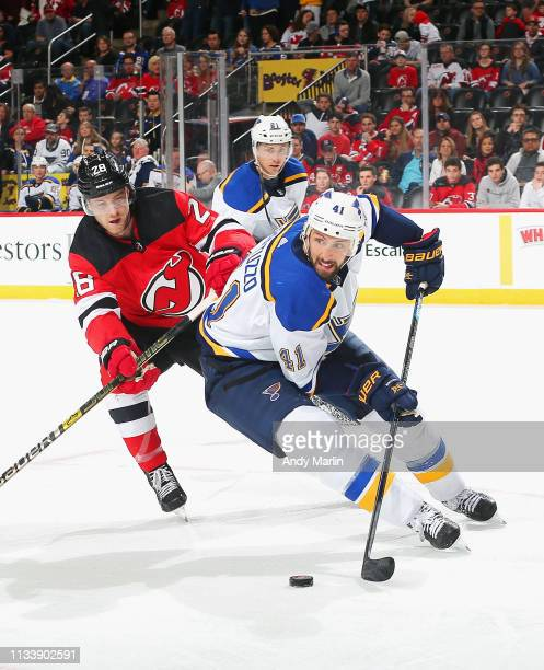 Robert Bortuzzo of the St Louis Blues plays the puck away from Damon Severson of the New Jersey Devils during the game at Prudential Center on March...