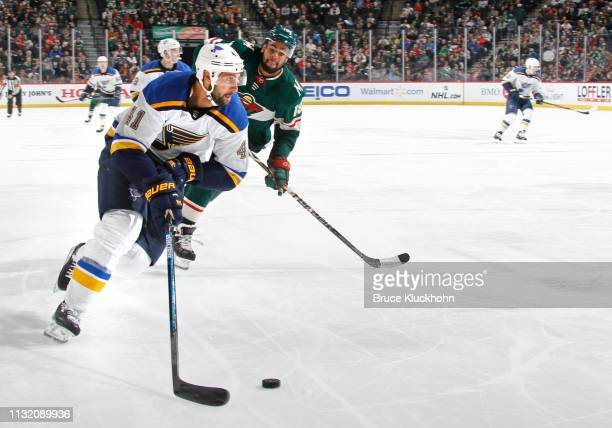 Robert Bortuzzo of the St Louis Blues skates with the puck as Jordan Greenway of the Minnesota Wild defends during a game at Xcel Energy Center on...