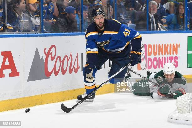 Robert Bortuzzo of the St Louis Blues skates with the puck past Chris Stewart of the Minnesota Wild in Game Three of the Western Conference First...