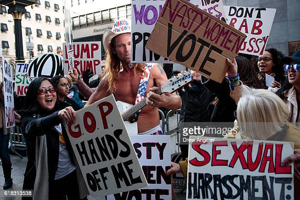 Robert Burck known as the 'Naked Cowboy' antagonizes protestors as they rally against Republican presidential candidate Donald Trump during a 'Nasty...