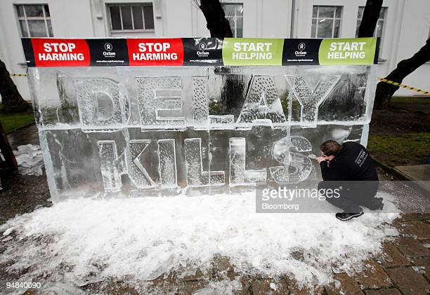 Robert Burkat carves an ice sculpture reading Delay Kills in an Oxfam International demonstration at the United Nations Climate Change Conference in...