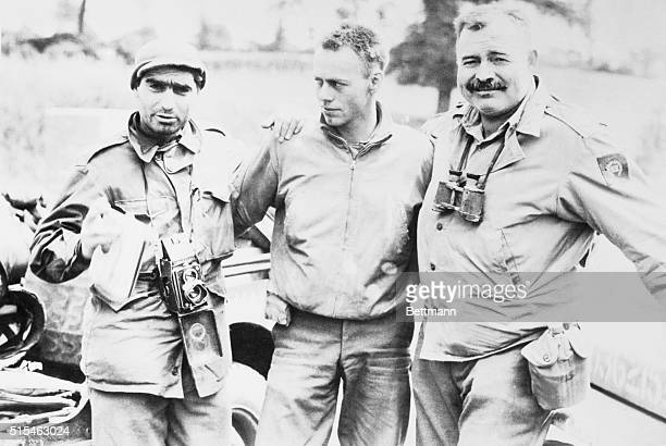 Robert Capa left photographer for Life magazine and Ernest Hemingway right stand with an unidentified soldier in this undated photo
