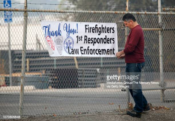 Robert Cooley, of Chico, hangs a sign thanking first responders for their work in the Camp Fire are seen across from the Cal Fire Incident Command...