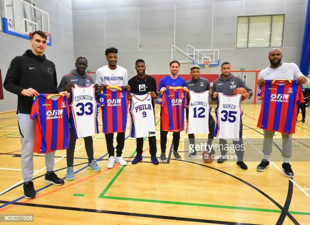 Robert Covington Dario Saric TJ McConnell and Trevor Booker of the Philadelphia 76ers pose with Football Legends Mamadou Sakho Timothy FosuMensah...