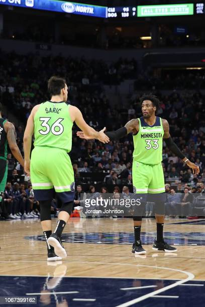 Robert Covington hifives Dario Saric of the Minnesota Timberwolves during the game against the Boston Celtics on December 1 2018 at Target Center in...