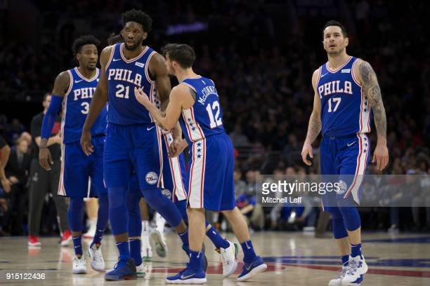 Robert Covington Joel Embiid TJ McConnell and JJ Redick of the Philadelphia 76ers walk to the bench during a timeout in the second quarter against...
