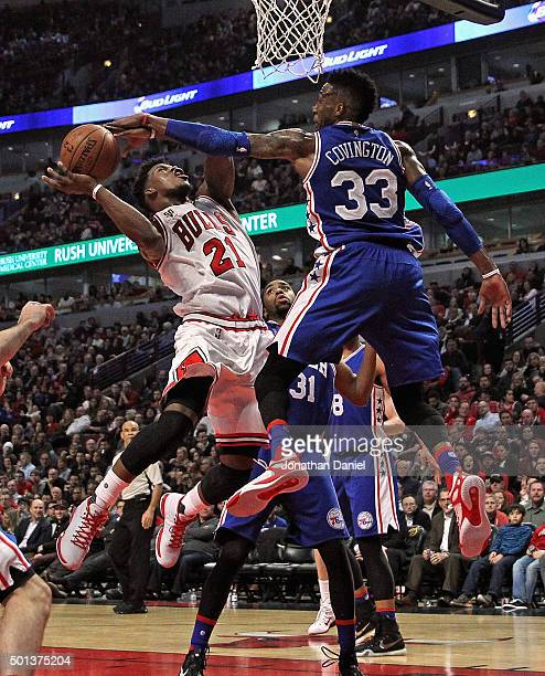 Robert Covington of the Philadelphia 76ers blocks a shot by Jimmy Butler of the Chicago Bulls at the United Center on December 14 2015 in Chicago...